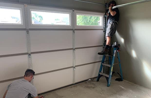 Two M&M Garage Doors contractors work on garage door service.