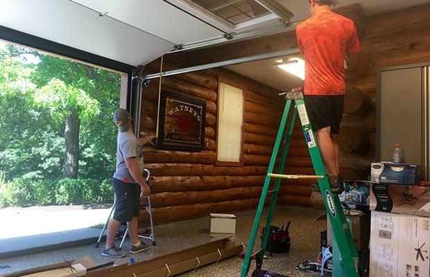 Two garage door service repair workers check the height of a garage door.