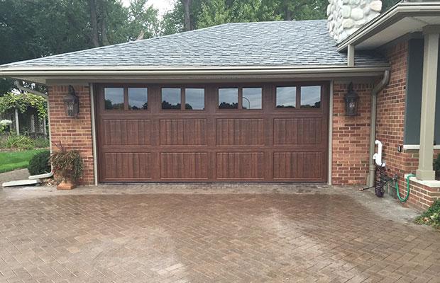 Brown garage door with glass windows closed after getting garage door service.
