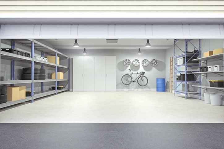 Open garage door with tools and shelves inside.