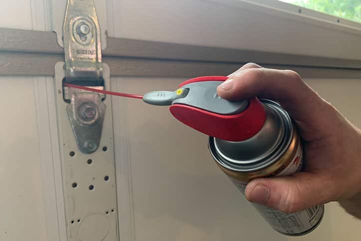 Hand holding lubrication for garage door hinge.