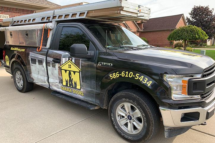 M&M Garage Doors work truck in driveway.